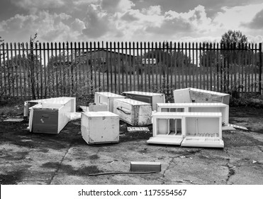 Several discarded fly-tipped fridges and freezers dumped on the ground in front of security fence, Clayton, Manchester, UK.