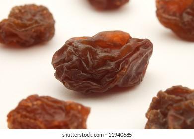 several dried raisins on white background