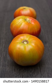 Several ecological tomatoes on a wooden table
