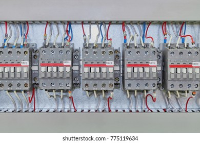 Several electrical contactor on a mounting panel in electrical closet. Modern contactors to start motors, pumps and other equipment. Contactors connected to the wires marked.