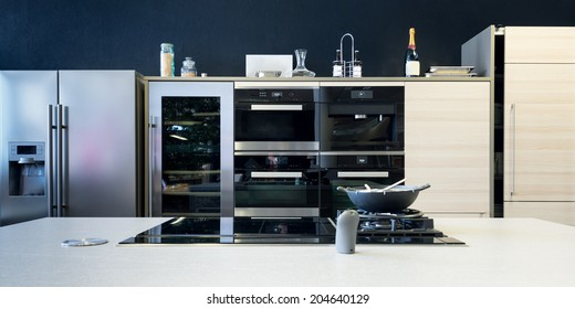 several electronic kitchen equipment with stove and timber front