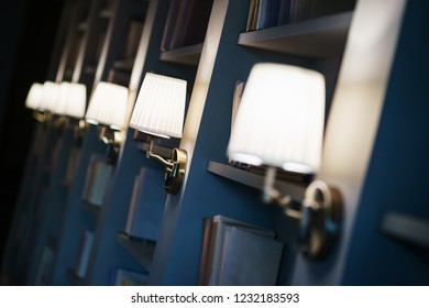 Several elegant, stylish and simple lamps sconces on the wall in the room. Interior details, lighting in the interior. Close-up and beautiful bokeh.
