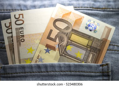Several fifty euro banknotes stuck out blue jeans pocket. Close up image. Hologram shining.
