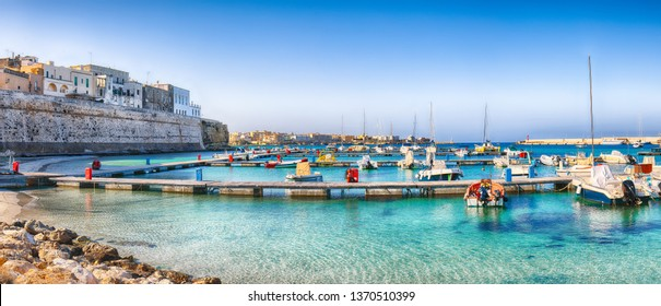 Several fishing boats at the Otranto harbour - coastal town in Puglia with turquoise sea. Italian vacation. Town Otranto, province of Lecce in the Salento peninsula, Puglia, Italy