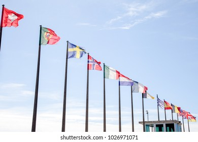 several flags of different countries are floating in the blue sky