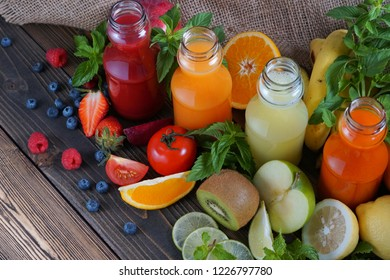 Several Fresh fruit juice squeezing put to glass bottle decorated by many kinds of fruit.