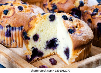 several fresh muffins close-up on a wooden stand