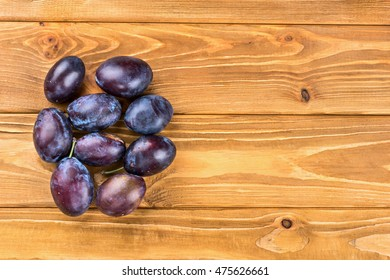 Several fresh plums on a blank wooden background