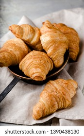 several freshly baked golden croissants on metal plate with handle, on linen napkin, on table