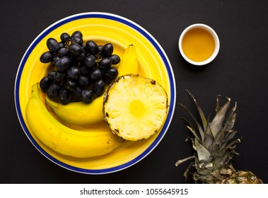 Several fruits on yellow plate.