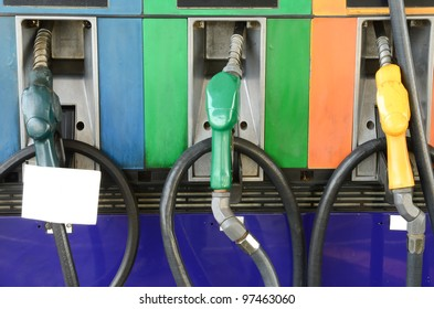 Several gasoline pump nozzles with white paper at petrol station