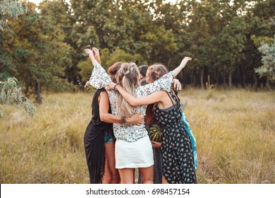 Several girls stand in a circle embracing each other