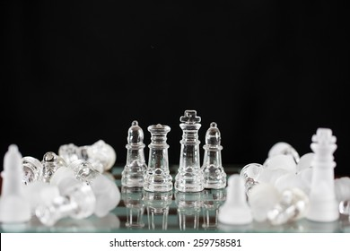 Several glass chess pieces left standing among quite a few fallen and disorganized pieces.
