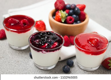 Several glass cups of yogurt with forest fruit berry jam and berries