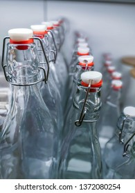 Several glass transparent bottles with lightning toggles swing-type flip-top closures (selective focus)