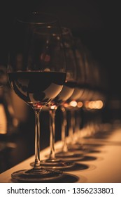 Several glasses of diferent kinds of red wine lined up in a dark, romantic wine tasting room.