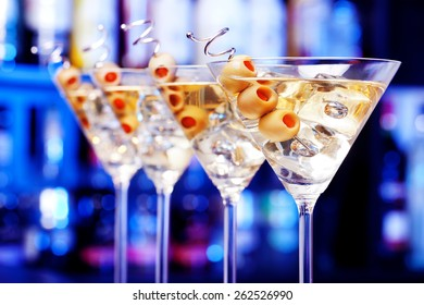 Several glasses of famous cocktail Martini, shot at a bar with shallow depth of field Ingredients: 55 ml gin 15 ml dry vermouth olives to garnish