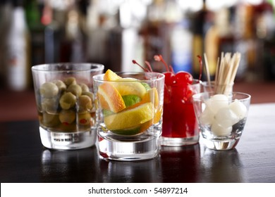 Several glasses filled with cocktail garnishes shot in a bar