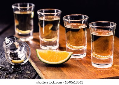 several glasses of Mezcal (or mescal) is an exotic alcoholic drink from Mexico, distilled, variation of tequila, consumed with orange, and with a larva inside