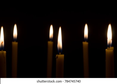 several glowing candles in dark background