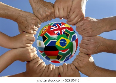 Several hands holding together in a circle around a soccer ball with flags