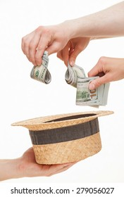 Several hands put dollars in a straw hat, white background