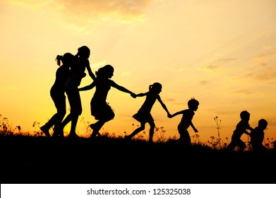 Several happy children running on meadow at summer sunset