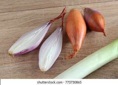Several heads of shallots. One bulb is cut in half. In the frame a stem leeks. Light wooden background. Close-up. Macro photography.