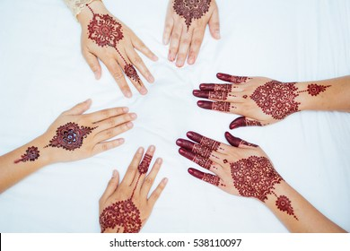 several henna design on hands
