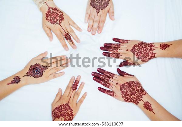 several henna design on hands
