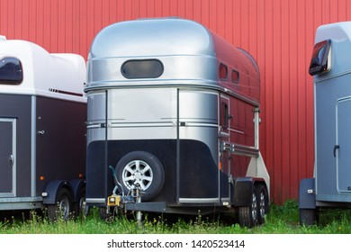 Several horse transportation trailers parked on the grass