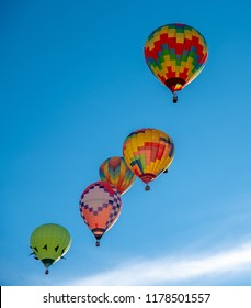 Several Hot Air Balloons rising in the morning sky as they drift to their destination in Reno, Nevada.