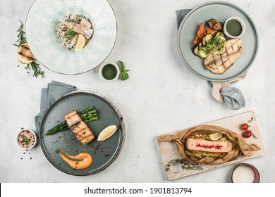 Several hot fish dishes cooked on the grill in different plates served by the chef on a light background, top view with a copy space. flat lay. Restaurant food.