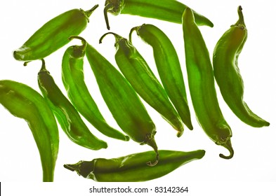 Several hot green hatch chili peppers isolated on white background