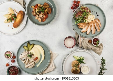 Several hot meat dishes cooked on the grill in different plates served by the chef on a light background, top view with a copy space. flat lay. Restaurant food.