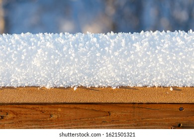 Several inches of fresh cold snow and frost accumulated on a wooden fence or deck railing outdoors in the daytime