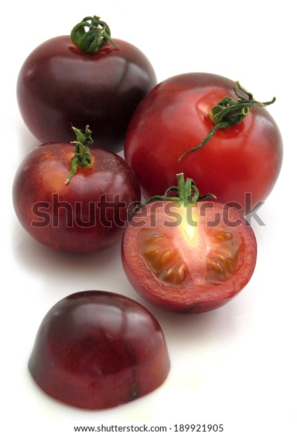 Several Indigo rose tomatoes, one chopped open