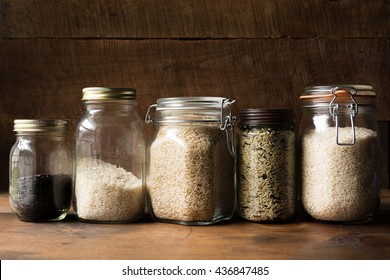 Several jars filled with different types of rice on a wooden shelf.