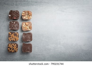 Several kinds of chocolate treats from above on a stone background.