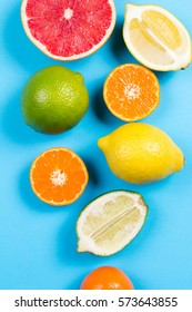 Several kinds of whole and cut citrus on a blue background