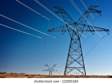 Several large high voltage power transmission towers silhouetted