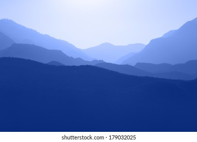 Several layers of mountain ranges stacked in blue silhouette.