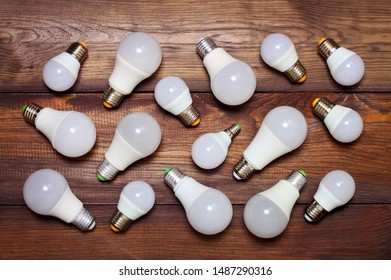Several led bulbs of different sizes and different bases on a wooden background.