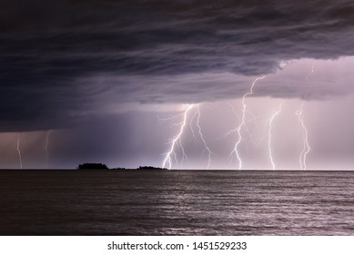 Several lightning strikes the sea not far from a small island, clouds in the sky, waves on the water.