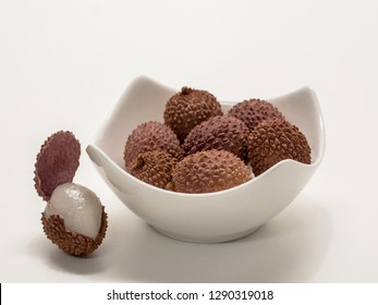Several lychee fruits, in a white bowl, next to it one with open shell