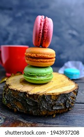 Several macarons of different colors on a dark background in a beam of light. Macaroons on a wooden background.