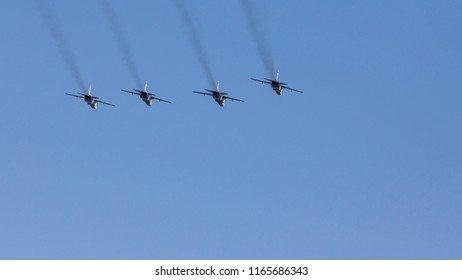 Several military fighters are flying in a formation against the blue sky