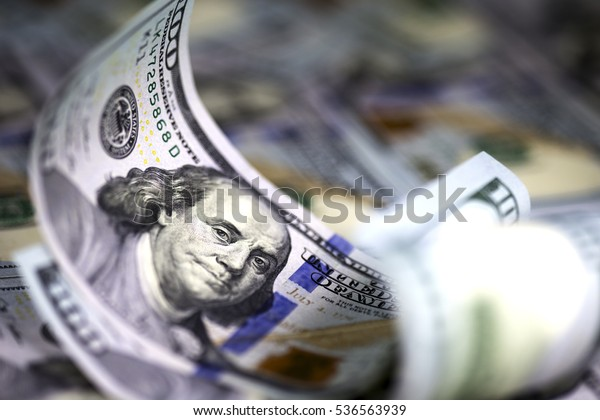 Several modern hundred us dollar bills, curved upward, lying on the background of hundred us dollar banknotes. Close up image. Selective light. Selective focus.