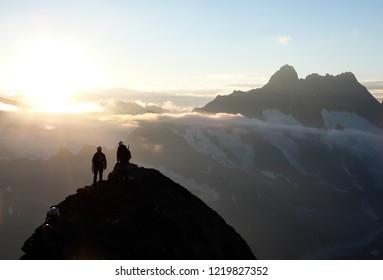 several mountain climbers on the famous Mittellegi Ridge on Eiger mountain in the Alps of Switzerkland heading to the summit at sunrise