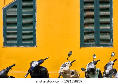 Several multicolored motorbike parked on the background of the bright yellow house facade with windows with wooden turquoise shutters in Hanoi in Vietnam. Horizontal.